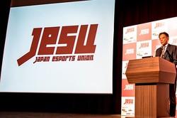 「日本eスポーツ連合」ロゴと代表理事の岡村秀樹氏