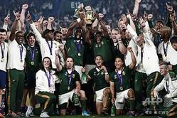 ラグビーW杯日本大会決勝、イングランド対南アフリカ。シリル・ラマポーザ大統領(中央右)とともに優勝トロフィーを掲げるシヤ・コリシ(中央左)ら南アフリカの面々(2019年11月2日撮影)。(c)CHARLY TRIBALLEAU / AFP