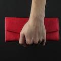 女性の手が赤い革財布を持っている