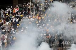 中国・香港で行われた「逃亡犯条例」改正案をめぐる抗議デモと警官隊が発射した催涙ガス(2019年6月12日撮影)。(c)Anthony WALLACE / AFP