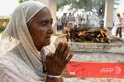 印パンジャブ州アムリツァルから約30キロ離れた村で、密造酒被害で死亡し火葬される犠牲者を悼む母親(2020年8月1日撮影)。(c)NARINDER NANU / AFP