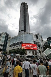 揺れが起きた中国・深センの超高層ビル「賽格広場」(中央)の近くに立つ人々(2021年5月18日撮影)。(c)STR / AFP