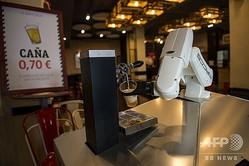 スペイン・セビリアにあるバー「ラ・ヒタナ・ロカ」で、ビールを注ぐロボット・バーテンダー「ビア・カート」(2020年5月17日撮影)。(c)CRISTINA QUICLER / AFP