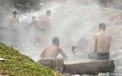 ボスニア・ヘルツェゴビナの首都サラエボ西郊イリジャで、天然温泉から流れ出た湯に漬かる移民ら(2021年1月21日撮影)。(c)ELVIS BARUKCIC / AFP