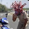 「新型コロナウイルスヘルメット」を被る警察官(画像は『The Economic Times 2020年3月29日付「Chennai cops use 'Corona' helmet to raise awareness on Covid-19」』のスクリーンショット)