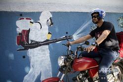 ジャイル・ボルソナロ大統領の顔をした新型コロナウイルスに消毒液を噴きかける防護服を着た人物の絵が描かれた屋外の壁の前をバイクで通る男性。ブラジル・リオデジャネイロで(2020年7月8日撮影)。(c)Mauro Pimentel / AFP