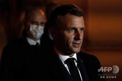 仏パリ近郊コンフランサントノリーヌで教師が殺害された事件を受け、学校前で記者団と話すエマニュエル・マクロン大統領(右、2020年10月16日撮影)。(c)ABDULMONAM EASSA / AFP