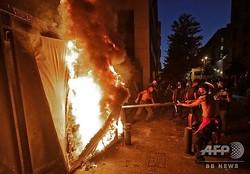 レバノン・ベイルートの国民議会近くで、バリケードの前に張られた覆いに火を放つデモ隊(2020年8月11日撮影)。(c)JOSEPH EID / AFP