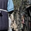 南アフリカ・ダーバンビルで、新型コロナウイルスの情報を提供する支援団体の職員とそれを見る子ども(2020年4月9日撮影)。(c)PIETER BAUERMEISTER / AFP