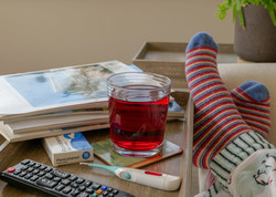 Feet of an adult resting at home while ill, with cosy striped socks and penguin pyjamas on, lying beside a table with a television remote control, thermometer, paracetamol, a red fruit drink in a glass and magazines to read.