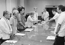(写真)要請文を沖縄総合事務局側に手渡す(左手前3人目から右へ)伊波、高里、屋良、北上田の各氏と赤嶺氏(左手前)=10日、那覇市