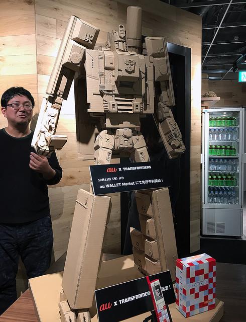 auのINFOBARトランスフォーマー、スマホ台付き3800円で発売。新宿に巨大段ボールロボあります