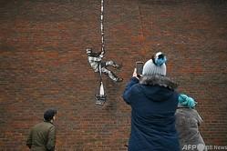英レディングの刑務所跡地の壁に出現した、覆面アーティストのバンクシーが描いたとみられるグラフィティ(2021年3月2日撮影)。(c)BEN STANSALL / AFP