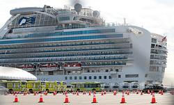 「ダイヤモンド・プリンセス」号と下船する乗客を待機するバス(C)日刊ゲンダイ