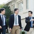 3人のビジネスパーソンが屋外を話しながら歩く