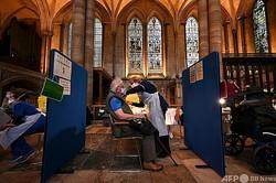 英イングランド南部のソールズベリー大聖堂で、新型コロナウイルスワクチンの接種を受ける男性(2021年1月20日撮影)。(c)JUSTIN TALLIS / AFP