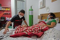 ブラジル・アマゾナス州マナウスの自宅で、新型コロナウイルス感染症(COVID-19)に罹患した母親の看護をする医師のマルコス・フォンセカ・バルボサさん(2021年1月10日撮影)。(c)MICHAEL DANTAS / AFP