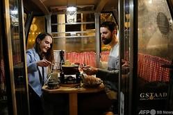 スイス・ベルンのレストランで、チーズフォンデュを食べるカップル(2020年11月16日撮影)。(c)STEFAN WERMUTH / AFP