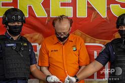 子どもにみだらな行為をしたとして逮捕されたフランソワ・カミーユ・アベロ容疑者(中央)。インドネシアの首都ジャカルタで開かれた記者会見にて(2020年7月9日撮影)。(c)Archie Bhadrika / AFP