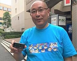 希少なポケベルユーザー・藤倉健さん。応援中のアイドルTシャツを着用し、取材に応じてくれた