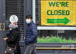 アイルランドの首都ダブリンで、マスクをして歩く人々(2020年10月19日撮影)。(c)PAUL FAITH / AFP