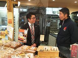 十勝産の小麦で作ったパンを前田さん(右)に勧める杉山さん(北海道帯広市で)