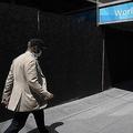 小売店の並ぶ通りをマスクを着けて歩く男性/Justin Sullivan/Getty Images