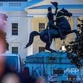 米首都ワシントンのホワイトハウスの前にあるラファイエット公園で、デモ隊が倒そうとした際に使ったロープやチェーンが巻き付いたままの第7代米大統領アンドリュー・ジャクソンの像(右奥、2020年6月22日撮影)。(c)Eric BARADAT / AFP
