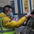 中国湖北省武漢のショッピングモールで、駐車場に入る車に乗っている人の体温を測定するマスクをした警備員(2021年1月22日撮影)。(c)Hector RETAMAL / AFP