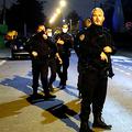 パリ北西のコンフランサントノリヌで16日、教員の男性が殺害された現場付近を警備する警察官=ロイター