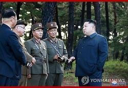 8月に行われた新兵器の試射を視察した金正恩委員長が、たばこを手に同行した軍幹部と話している=(朝鮮中央通信=聯合ニュース)≪転載・転用禁止≫