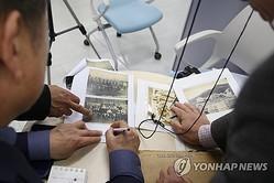 集団訴訟への参加を希望する強制徴用被害者の遺族が申請窓口で資料の説明をする様子=5日、光州(聯合ニュース)