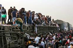 エジプト首都カイロ北郊で脱線転覆した列車の車両に上った人たち(2021年4月18日撮影)。(c)Ayman AAREF / AFP