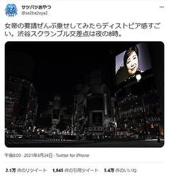 真っ暗な東京・渋谷の大型スクリーンに、小池百合子都知事の顔が浮かぶ画像。合成写真として投稿されたが、実際の風景と誤解させる形で拡散された(ツイッターより)