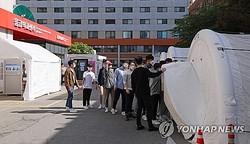 国立中央医療院の専用診療所で検体採取を受けるため、陰圧テントに入る義務警察ら=13日、ソウル(聯合ニュース)