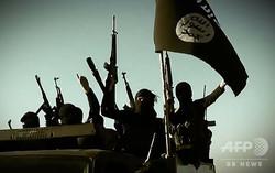 イラク・アンバル州で旗や武器を掲げるイスラム過激派組織「イスラム国(IS)」の戦闘員。IS系のアルフルガン・メディアが公開した動画より(2014年3月17日公開、資料写真)。(c)AFP=時事/AFPBB News