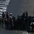 ミャンマー・ヤンゴンで行われたクーデターに対する抗議デモの参加者に向かい銃器を構える警察官ら(2021年3月1日撮影)。(c)STR / AFP