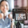 ソーシャルメディアで若いブロガーのオンライン放送とデジタルカメラの写真をクローズアップ