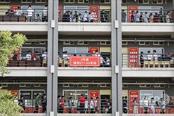 中国中部河南省で、大学入学試験「高考」の試験の前に会場外に並ぶ生徒たち(2020年7月7日撮影)。(c)AFP