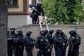 9日、ドイツ東部ハレで、シナゴーグ(ユダヤ教礼拝所)の墓地の壁を登る警官(EPA時事)