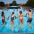 英ロンドン南東部で、プールに飛び込む子供たち(2020年7月31日撮影)。(c)Tolga Akmen / AFP