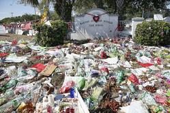 米フロリダ州のマージョリー・ストーンマン・ダグラス高校前に置かれた追悼の花束やキャンドル(2018年3月14日撮影)。(c)RHONA WISE / AFP
