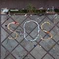 香港理工大学で、服などで地面に形作られた「SOS」の文字(2019年11月21日撮影)。(c)NICOLAS ASFOURI / AFP
