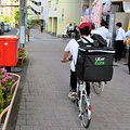 歩行者が自転車に衝突された現場。情報提供を求める警視庁の立て看板が設置され、その前を配達員とみられる人たちが自転車で次々走り抜けた=2020年5月14日、東京都中野区、角詠之撮影