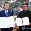 「平壌共同宣言」に署名した文大統領(左)と金委員長(写真共同取材団)=19日、平壌(聯合ニュース)