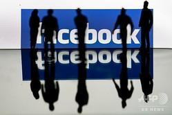 米SNS大手フェイスブックのロゴと人影(2020年2月14日撮影)。(c)Kenzo TRIBOUILLARD / AFP