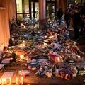 仏パリ近郊コンフランサントノリーヌの、教師が殺害された学校の入り口に供えられた花の前に立つ人々(2020年10月17日撮影)。(c)Bertrand GUAY / AFP