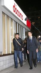 市川市のドコモショップ前で山岡さん(左)を出迎えたドコモ幹部。山岡さんの表情は疲れきっていた