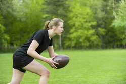 Girl playing rugby together outside in summer