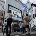 緊急事態宣言の解除を発表する安倍晋三首相の記者会見に聞き入る人々(新宿・アルタ前)